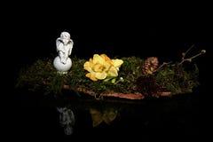 Ángel y flor delante de un fondo negro Imagen de archivo