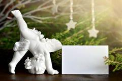 Ángel y tarjeta de Navidad en blanco Imagenes de archivo
