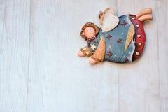Ángeles de cerámica de la Navidad en un fondo de madera Foto de archivo