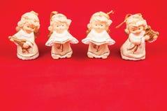 Ángeles de la Navidad en un fondo rojo Imagenes de archivo