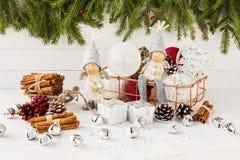Ángeles de la Navidad y bolas de la Navidad en la cesta, árbol de navidad en el fondo de madera blanco Imagen de archivo libre de regalías