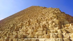Ángulo bajo cercano de la gran pirámide debajo de los cielos azules en Giza, Egipto foto de archivo libre de regalías