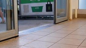 Ángulo bajo de la gente con caminar a través de las puertas en el superstore almacen de metraje de vídeo
