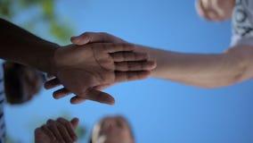 Ángulo bajo de los amigos positivos que llevan a cabo las manos juntas