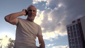 Ángulo bajo de un hombre mayor que habla en el teléfono al aire libre almacen de metraje de vídeo