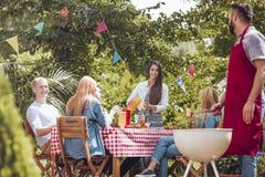 Ángulo bajo del hombre que asa a la parrilla la comida y a amigos felices durante fiesta de cumpleaños en el jardín fotos de archivo libres de regalías