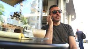 Ángulo bajo del hombre que usa el teléfono móvil en un café almacen de video