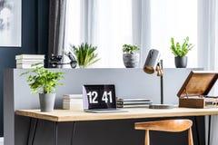 Ángulo lateral de un escritorio de madera con un ordenador portátil que muestra el tiempo, planta, l fotografía de archivo libre de regalías