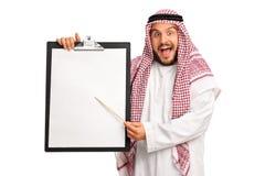 Árabe emocionado que sostiene un tablero y que señala en él Imagenes de archivo