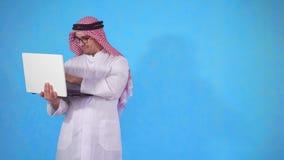 Árabe feliz con un ordenador portátil que él aprendió sobre ganar metrajes