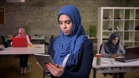 Árabe focalizado sério fêmea no hijab azul que está e que datilografa em sua tabuleta, fêmeas árabes no fundo, moderno vídeos de arquivo