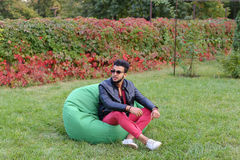 Árabe Guy Musingly Looks Aside, resto e assento na cadeira em Gree foto de stock royalty free