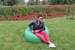 Árabe Guy Musingly Looks Aside, resto e assento na cadeira em Gree imagens de stock royalty free