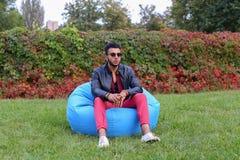 Árabe Guy Musingly Looks Aside, resto e assento na cadeira em Gree fotografia de stock royalty free