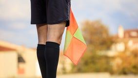 Árbitro auxiliar del fútbol en el campo que sostiene la bandera Fondo enmascarado Fotografía de archivo libre de regalías