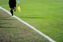 Árbitro auxiliar en la acción en un campo de fútbol Foto de archivo libre de regalías