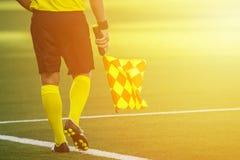 Árbitro auxiliar que se mueve a lo largo de la línea lateral durante un matc del fútbol Fotografía de archivo libre de regalías