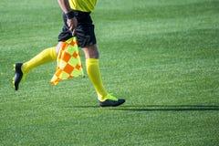 Árbitro auxiliar que se mueve a lo largo de la línea lateral durante un matc del fútbol Imágenes de archivo libres de regalías
