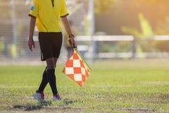 Árbitro auxiliar que se mueve a lo largo de la línea lateral durante un partido de fútbol Imagen de archivo libre de regalías