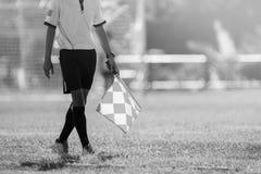 Árbitro auxiliar que se mueve a lo largo de la línea lateral durante un partido de fútbol Imagen de archivo