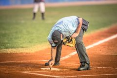 Árbitro del béisbol mientras que limpia la base Imagen de archivo libre de regalías