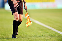Árbitro del fútbol con la bandera en la línea lateral Imagen de archivo