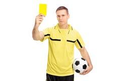 Árbitro del fútbol que muestra una tarjeta amarilla Foto de archivo libre de regalías