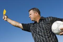 Árbitro del fútbol que sostiene la tarjeta amarilla foto de archivo libre de regalías