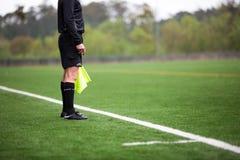 Árbitro do futebol ou do futebol que está no campo de grama artificial verde foto de stock