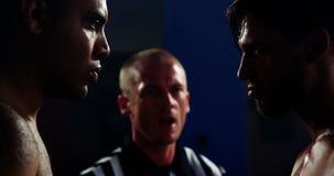 Árbitro que obra recíprocamente con los boxeadores antes de comenzar el partido metrajes