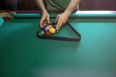 Árbitro que prepara las bolas de billar en la mesa de billar Imagenes de archivo