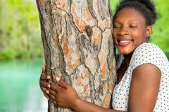 Árbol africano del abarcamiento de la muchacha en bosque Fotografía de archivo libre de regalías