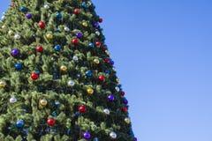 Árbol brillantemente adornado del Año Nuevo en la calle con el cielo azul Imagenes de archivo