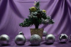 Árbol, chucherías y regalos de la decoración de la Navidad en fondo brillante de las luces imagenes de archivo