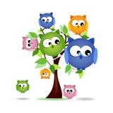 Árbol con la familia colorida de los búhos Fotos de archivo