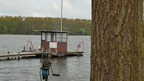 Árbol con un barco en el embarcadero en fondo en el lago almacen de metraje de vídeo