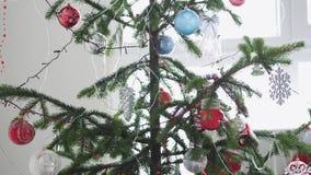 Árbol de abeto adornado la Navidad elegante por la ventana Cámara lenta 3840x2160 almacen de video
