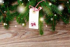 Árbol de abeto con la etiqueta de la Feliz Navidad para el 24 de diciembre Imagen de archivo libre de regalías