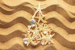 Árbol de abeto hecho de las estrellas de mar en fondo de la arena Fotografía de archivo libre de regalías