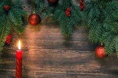 Árbol de Cristmas con la vela y bolas rojas en superficie de madera Foto de archivo