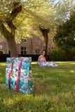 Árbol de hierba de la mujer que se sienta relajada, Groot Begijnhof, Lovaina, Bélgica foto de archivo