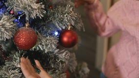 Árbol de la Navidad de adornamiento de la familia joven y del Año Nuevo junto en el pórtico Cierre para arriba metrajes