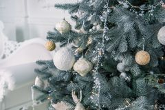 Árbol de la Navidad, del Año Nuevo adornado con las guirnaldas y juguetes en un cuarto brillante Imagenes de archivo
