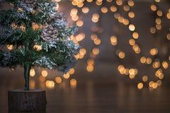 Árbol de Mini Christmas con las luces y el fondo de madera foto de archivo libre de regalías