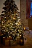 Árbol de navidad acogedor con las luces de la Navidad y las cajas de presentes Colores calientes, crepúsculo íntimo Foto de archivo