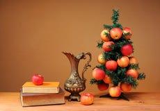 Árbol de navidad adornado con con las manzanas y los libros Imagen de archivo