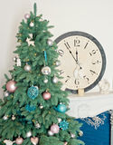 Árbol de navidad adornado con el reloj cerca del fireplacw en el interior blanco Fotos de archivo