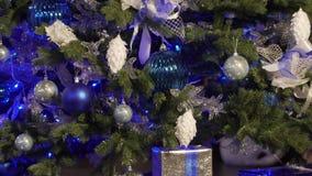 Árbol de navidad adornado con las guirnaldas y los juguetes azules brillantes el abeto adornado con los juguetes azules Un abeto  almacen de metraje de vídeo