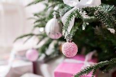 Árbol de navidad adornado con los juguetes en el color de plata y rosado En él vemos los globos con de las cintas y las luces Fotografía de archivo libre de regalías