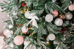 Árbol de navidad adornado con los juguetes en el color de plata y rosado En él vemos los globos con de las cintas y las luces Fotos de archivo libres de regalías